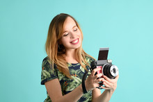 Pretty Young Woman With Instant Camera