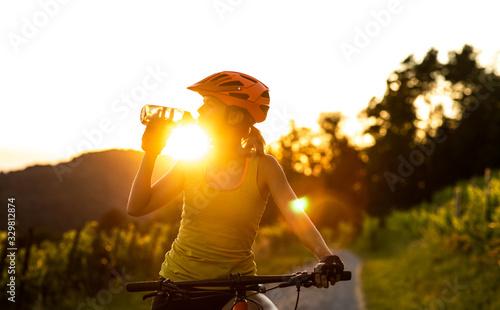 Pretty, young woman biking on a mountain bike enjoying healthy active lifestyle Canvas