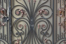 Colored Metal Texture Of Black Forged Rods In A Pattern On A Gray Wall