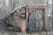 Old Ruined Brown Brick Building With Rusty Iron Door Overgrown With Dry Vegetation On The Street