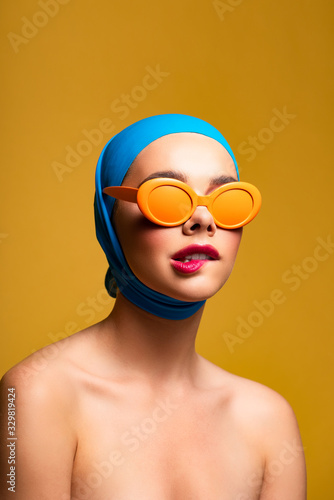 fashionable naked girl in scarf and orange sunglasses biting lip, on yellow