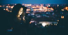 Woman Using Smartphone At Dusk...
