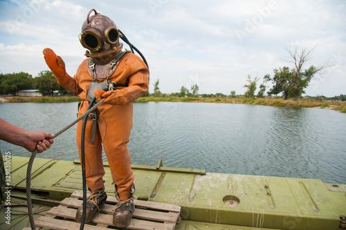 Fényképezés Diver immerses in a vintage deep sea diving suit