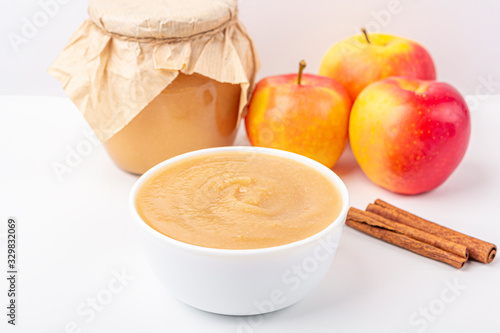 Photo Fresh homemade applesauce in white bowl and jar with fruit puree on white table