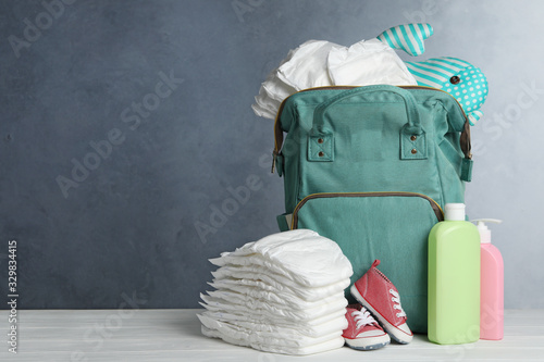 Photo Bag with diapers and baby accessories on white wooden table against grey background