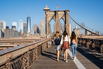 Three girls walking on the Brooklyn Bridge with the New York skyline on the back