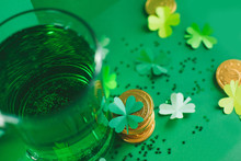 Saint Patricks Day Backdrop With Bear Cup With Ale, Stack Of Chocolate Coins, Green Four-leafed Paper Shamrocks