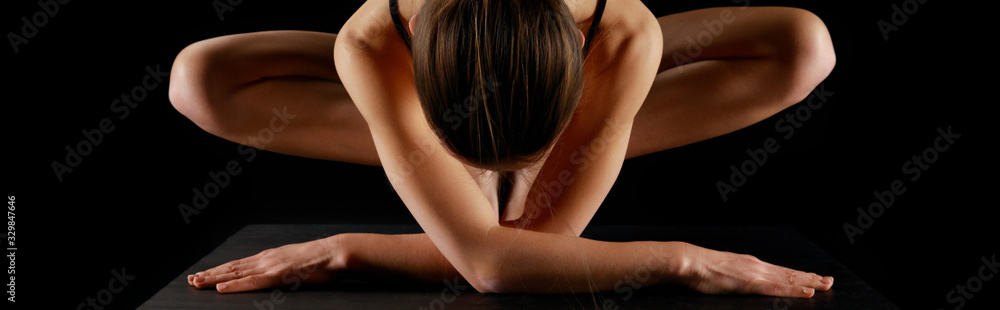 Fototapeta panoramic shot of athletic woman practicing yoga isolated on black