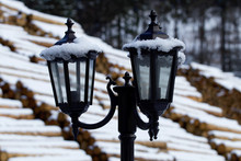 Snowy Lamps And Wooden Logs