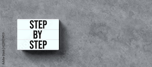 Fototapety, obrazy: lightbox with message STEP BY STEP on concrete background