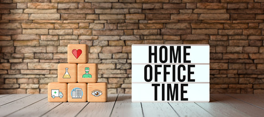 cubes with health-symbols stacked as a pyramid and lightbox with text HOME OFFICE TIME in front of a brick wall