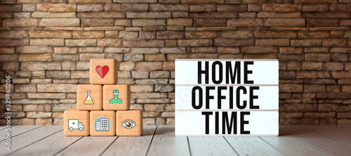 cubes with health-symbols stacked as a pyramid and lightbox with text HOME OFFICE TIME in front of a brick wall - 329860206