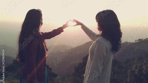 Female Friends Making Heart Shape From Hands In Front Of Sun Against Sky - fototapety na wymiar