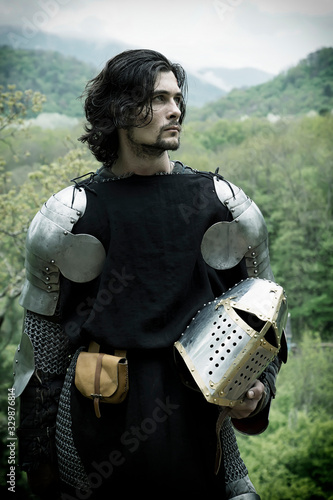 Canvas-taulu Young Knight Holding Helmet While Standing In Forest