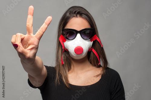 ragazza che fa il segno di vittoria con la mascherina anti virus Wallpaper Mural