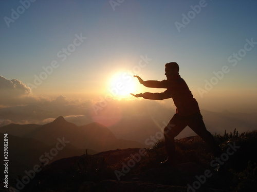 Fototapety, obrazy: Optical Illusion Of Man Holding Sun While Standing On Mountain During Sunset