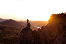 Hipster Travel Man With Backpack Enjoying Freedom Looking On Amazing At Sunset. Traveler On Cliff Mountains Over Great Canyon.