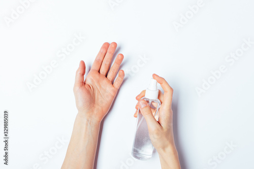 Leinwand Poster Woman's hands applying alcohol disinfectant spray