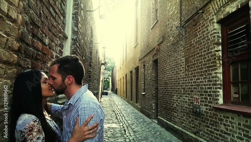 Fotografie, Obraz Side View Of Romantic Couple Kissing At Alley