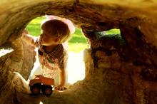 Boy Seen Through Hollow Log