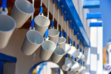 White Mugs Hang In A Greek Str...