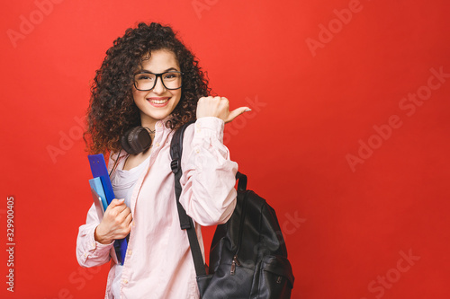 Young curly student woman wearing backpack glasses holding books and tablet over isolated red background Canvas-taulu