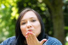 Close-up Portrait Of Woman Blowing Kiss Against Trees At Park