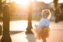Cute Girl Wearing Tutu Standing On Footpath At Park During Sunset