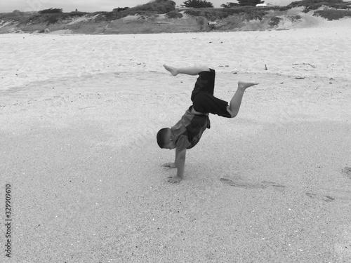 Fotografie, Tablou Full Length Of Boy Doing Handstand At Beach