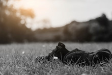 Black And White Image Lost Children's Shoes On Grass Field, The Forgotten Paire Of School Kid Shosein The Park, Lost Child, International Missing Child, Abandoned Concept.