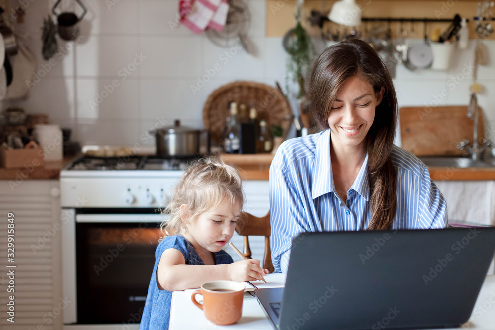 Fototapeta Working mom works from home office with kid. Happy mother and daughter. Woman and cute child using laptop. Freelancer workplace in cozy kitchen. Female business, career. Lifestyle family moment.