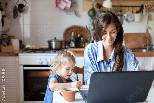 Obraz Working mom works from home office with kid. Happy mother and daughter. Woman and cute child using laptop. Freelancer workplace in cozy kitchen. Female business, career. Lifestyle family moment. - fototapety do salonu