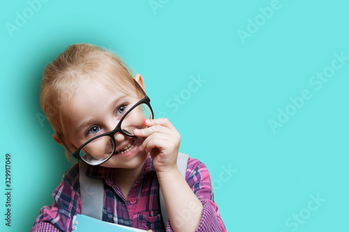 Vászonkép Cute little blonde girl in glasses with a backpack on a blue background