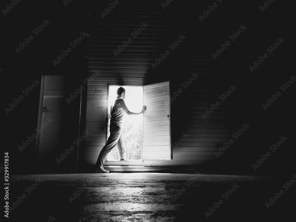 Fototapeta Side View Of Young Man Standing At Doorway In Darkroom