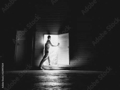 Obraz Side View Of Young Man Standing At Doorway In Darkroom - fototapety do salonu