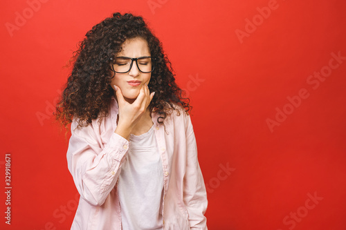 Fotografia Young curly woman over isolated red background touching mouth with hand with painful expression because of toothache or dental illness on teeth