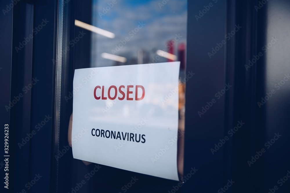 Fototapeta Woman hangs a card with information about the store closing on a shop window due to the coronavirus