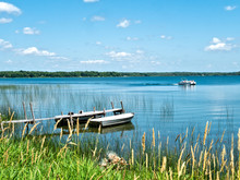 Beautiful Minnesota Lake Scene With Reeds On Shore, Two Aluminum Fishing Boats Bobbing Gently At A Wooden Dock And A Passing Pontoon On A Sunny Day With Blue Sky And Fluffy White Clouds.