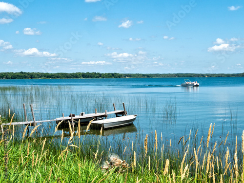Obraz na plátne Beautiful Minnesota lake scene with reeds on shore, two aluminum fishing boats bobbing gently at a wooden dock and a passing pontoon on a sunny day with blue sky and fluffy white clouds