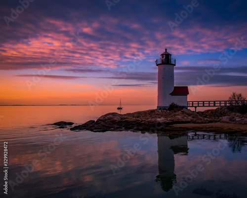 Photo Sunset reflections at Annisquam Lighthouse with sail boat - Gloucester, Massachusetts