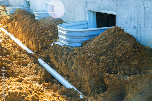 Fototapeta Plastic piping and a rainpipe against and around the a drainpipe in ground house