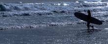Female Surfer Walking Against Sea At Beach