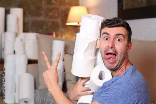 Obraz Man stocking up toilet paper at home - fototapety do salonu