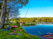 Shirtless Boy Fishing In Lake Against Sky