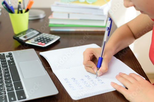 Cropped Image Of Girl Writing On Book By Laptop Wallpaper Mural