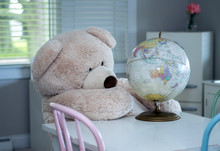 A Giant Teddy Bear Looks Over A Toy Globe, Perhaps Looking For A New Place To Vacation