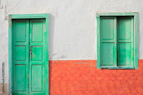 Photo A green door and a green window in a wall with red bricks.