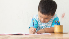 Boy Writing In Book At Table Against Wall