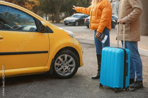 Fototapeta Couple of tourists catching taxi on city street obraz na płótnie
