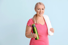 Sporty Mature Woman With Bottle Of Water On Color Background